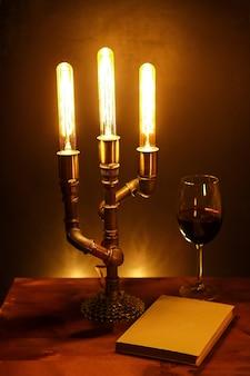 Een stilleven met handgemaakte elektrische lamp, boek en glas wijn