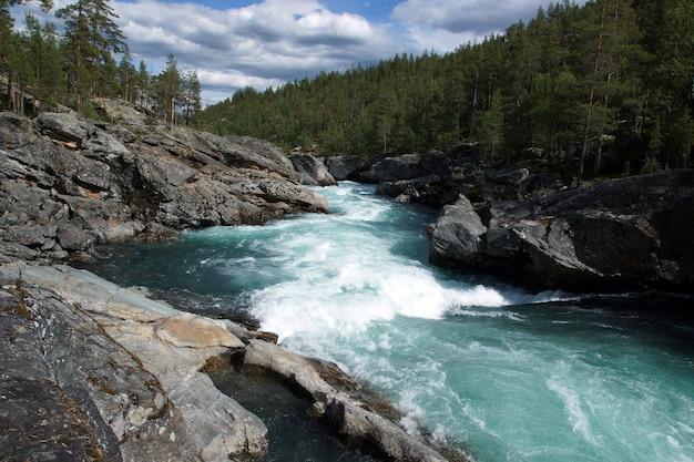 Een stormachtige rivierstroom met geluid stroomt door de rotsen en het bos in noorwegen, helder transparant blauw water.