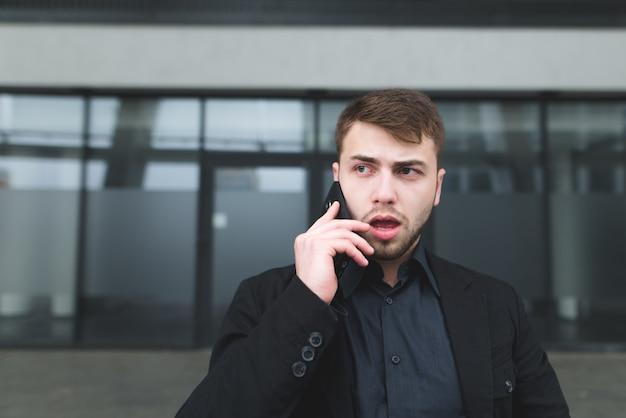 Een straatportret van een serieuze jongeman met een baard die op een mobiele telefoon tegen een donkere muur communiceert
