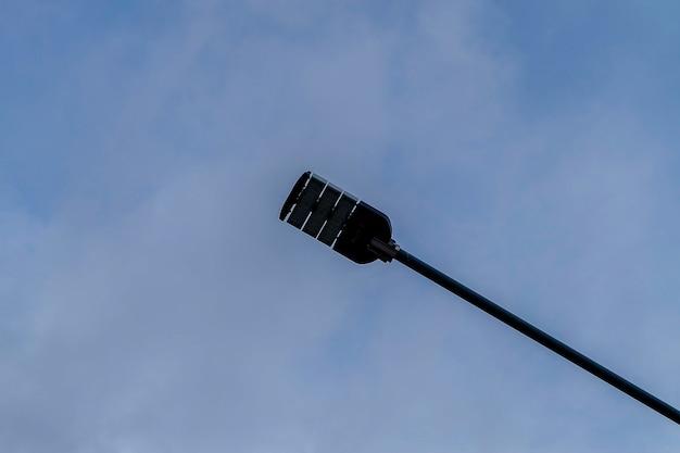 Een straatverlichting lamp op een paal tegen de blauwe hemelwolk achtergrond