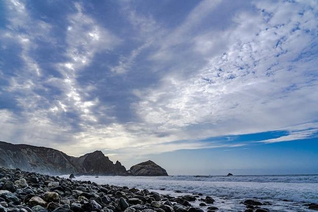 Een strand bedekt met zwarte rotsen onder schitterende wolken