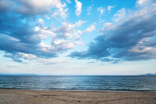 Een strand en de egeïsche zee, gedeeltelijk bewolkte hemel, griekenland