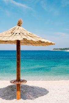 Een strand met stro bedekte parasol tegen de blauwe lucht en azuurblauw water op een zandstrand