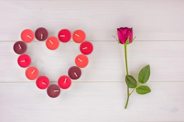 Een streng van rode roos en geurige kaarsen in hartvorm op een witte houten tafel.