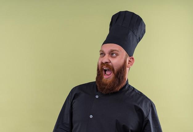 Een stressvolle bebaarde chef-kok man in zwart uniform huilen en negativiteit uiten op een groene muur