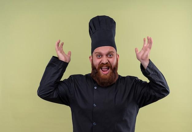 Een stressvolle bebaarde chef-kokmens in zwart uniform gooit zijn handen in de lucht op een groene muur