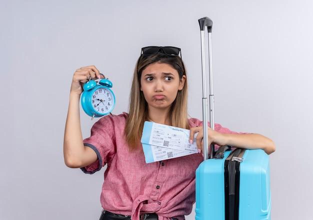 Een stressvolle jonge vrouw die een rood shirt en een zonnebril draagt en naar de zijkant kijkt terwijl ze een wekker met vliegtickets en een blauwe koffer op een witte muur houdt