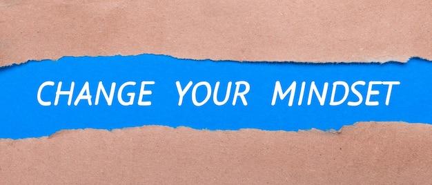 Een strook blauw papier met de woorden change your miindset tussen het bruine papier. uitzicht van boven