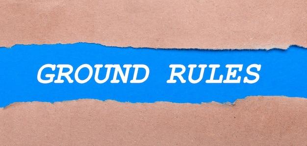 Een strook blauw papier met het opschrift ground rules tussen het bruine papier. uitzicht van boven