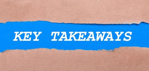 Een strook blauw papier met het opschrift key takeaways tussen het bruine papier. uitzicht van boven