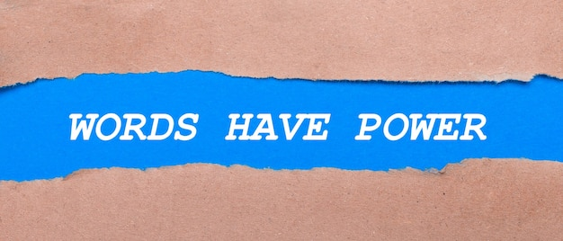 Een strook blauw papier met het opschrift woorden hebben kracht tussen het bruine papier