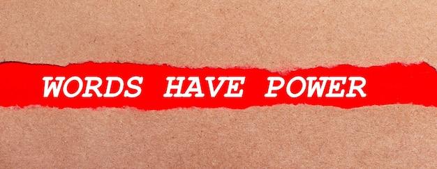 Een strook rood papier onder het gescheurde bruine papier. witte letters op rood papier woorden hebben kracht. uitzicht van boven