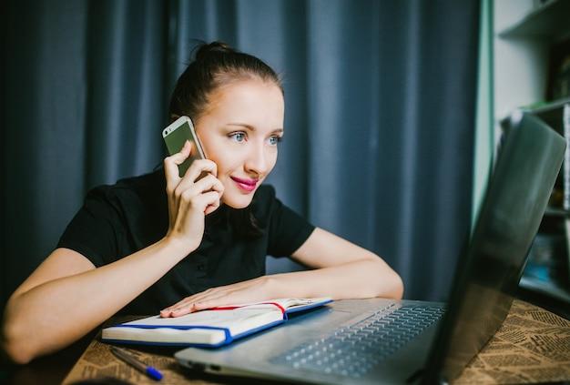 Een student die aan de telefoon zit en achter de laptop zit