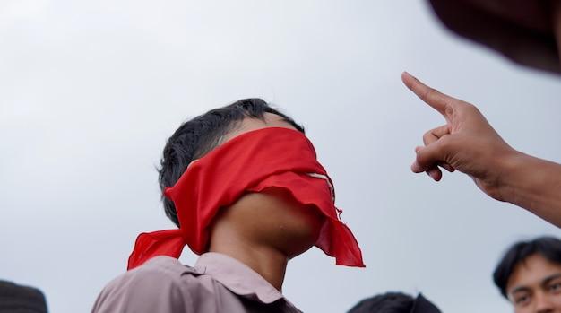 Een student die een nummer raadspel speelt met zijn hoofd bedekt met een doek