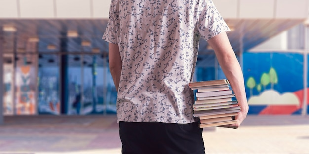 Een student die een stapel boeken vasthoudt, zware papieren schoolboeken draagt, motivatieconcept