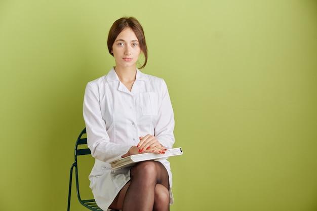 Een student in een witte medische jas zit op een stoel met een boek in haar handen. geïsoleerd