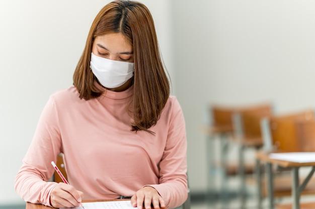 Een student met een masker zit in een klaslokaal op de universiteit.