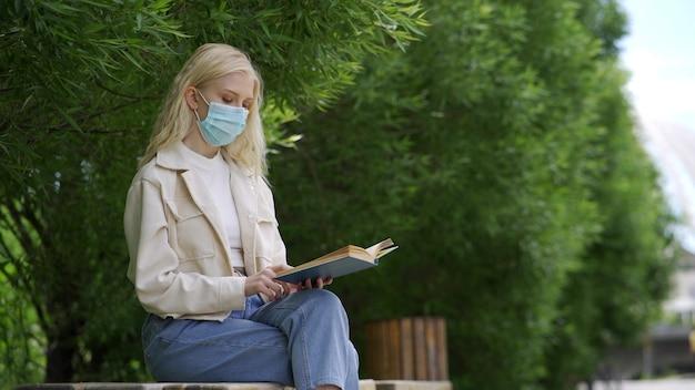 Een student met een medisch masker leest een boek in het park. buiten studeren tijdens de coronavirusepidemie. 4k uhd