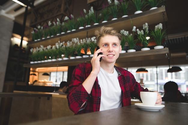 Een student praat telefonisch in het café en lacht.