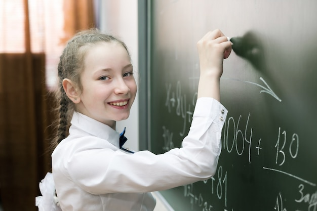 Een student van de meisjes vrouwelijke basisschool schrijft op het bord.