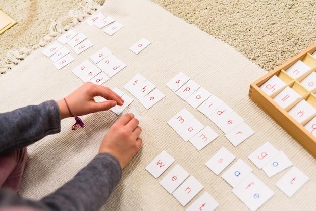 Een student van een montessorischool die kaarten met letters gebruikt om woorden en zinnen op een mat te schrijven.