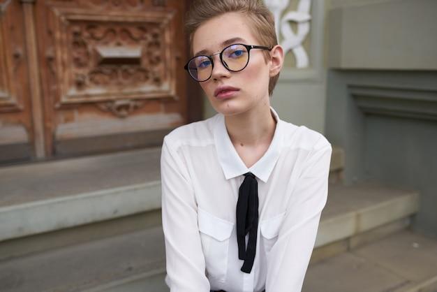 Een studente in spijkerbroek en overhemd zit op de trap bij het gebouw en heeft een bril op haar gezicht