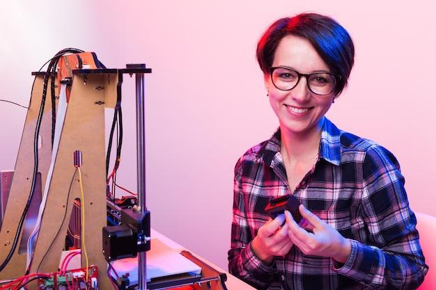 Een studentenvrouw drukt een prototype af op een 3d-printer.