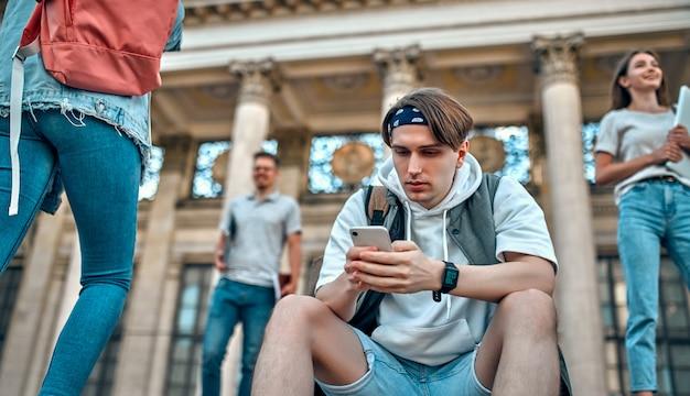 Een studentjongen met rugzak zit op de trap bij de campus en gebruikt zijn smartphone