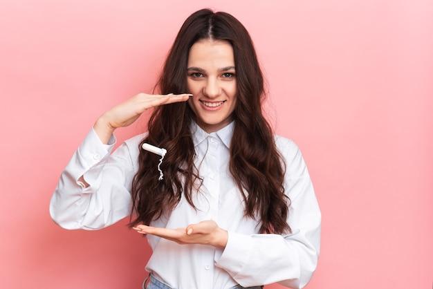 Een studio-opname van een meisje met een tampon in haar hand in een menstruatie-applicator. ruimte voor de tekst. het concept van vrouwelijke hygiëne.