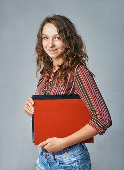 Een studioportret van een gelukkige jonge vrouwelijke student