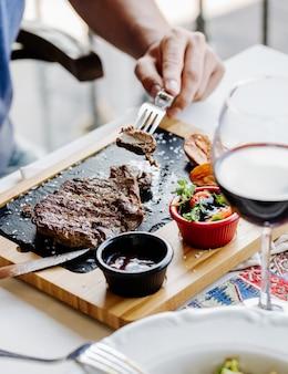 Een stuk biefstuk met vork nemen.
