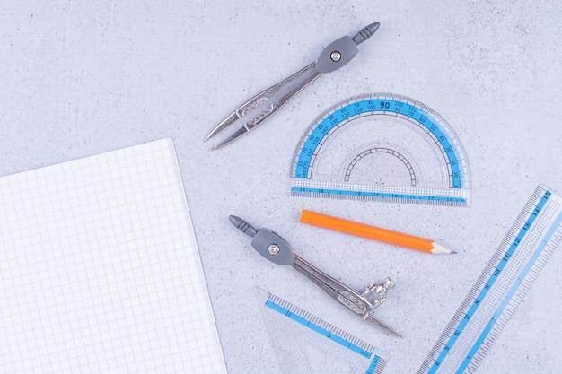 Een stuk blanco papier met pen, houtskoolpotlood, liniaal en verdelers eromheen