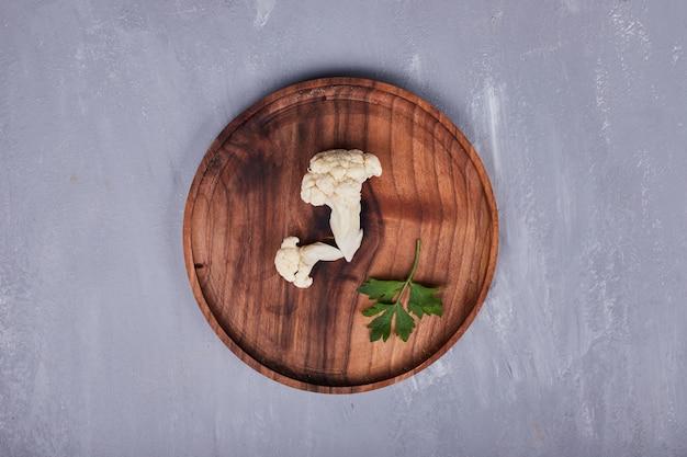 Een stuk bloemkool met peterselie in een houten schaal.