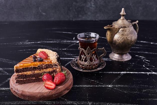 Een stuk chocoladetaart met klassiek theeservies op donkere achtergrond.