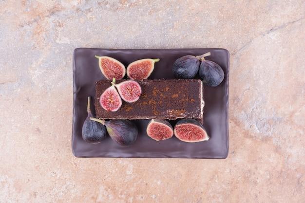 Een stuk chocoladetaart met vijgen en cornels