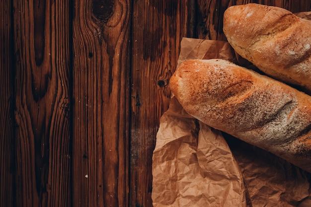 Een stuk frans stokbrood op het ambachtelijke papier en donkere houten achtergrond