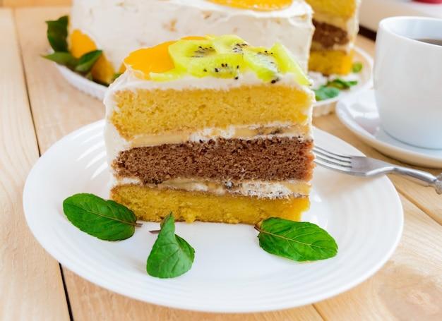Een stuk fruitcake (kiwi, sinaasappel, muntblaadjes) op een witte plaat op houten achtergrond close-up en een kopje thee