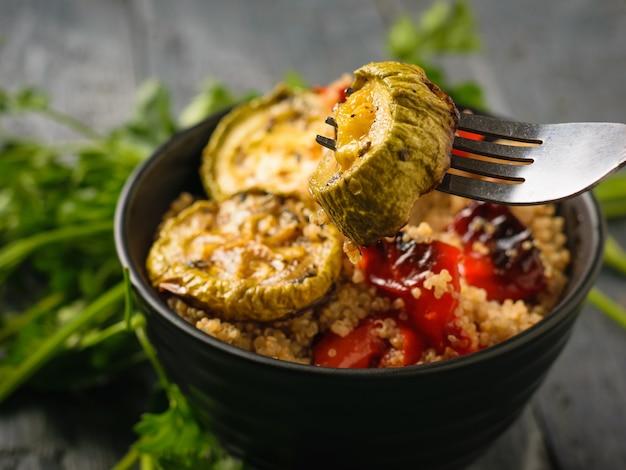 Een stuk gebakken courgette op een vork en quinoasalade op een zwarte lijst. vegetarisch gerecht. natuurlijk plantaardig voedsel. het uitzicht vanaf de top.