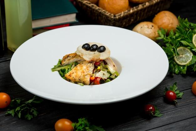 Een stuk gegrilde visfilet met groene salade en bessen in een witte plaat.