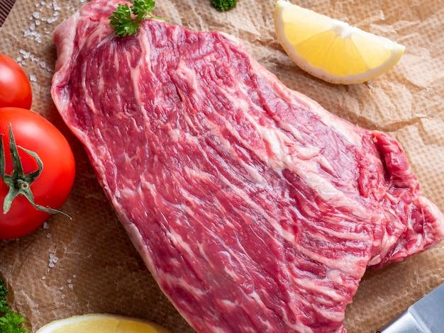 Een stuk gemarmerd rundvlees ligt op perkament omgeven door kruiden, knoflook, zout. bovenaanzicht, plat gelegd. voedsel samenstelling