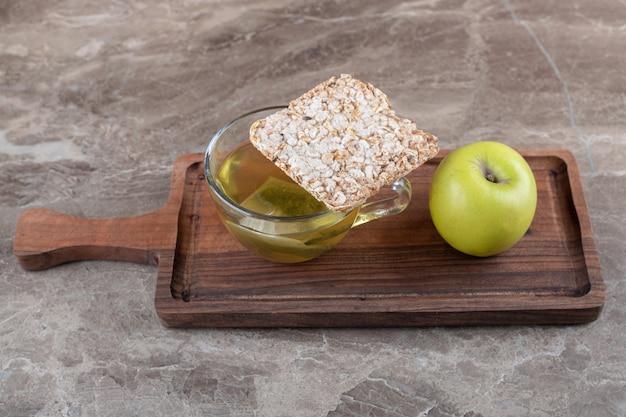 Een stuk gepofte rijstwafel, thee en appel, op het houten blad, op het marmeren oppervlak