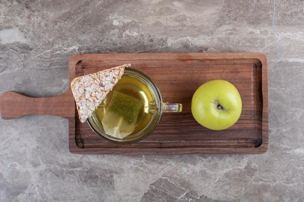 Een stuk gepofte rijstwafel, thee en appel, op het houten dienblad, op de marmeren achtergrond.