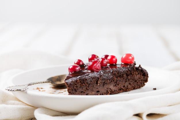 Een stuk glutenvrije brownie cake met chocoladesuikerglazuur, versierd met veenbessen, op een witte plaat, op een licht houten tafel close-up. wazig lichte achtergrond. gezonde desserts.