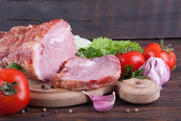 Een stuk ham en groenten op een houten achtergrond. vleeswaren product