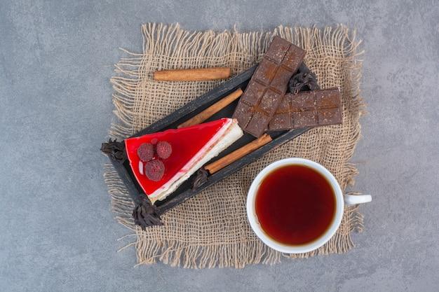 Een stuk heerlijke cake met kopje thee en chocolaatjes op een zak.