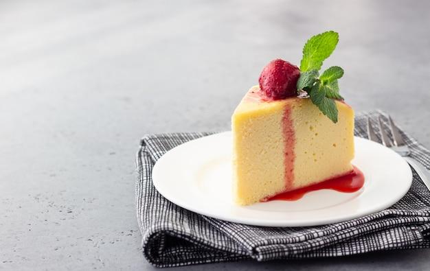 Een stuk japanse katoenen cheesecake met munt en aardbei.