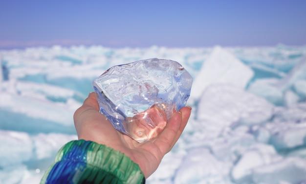 Een stuk kristal transparant ijs in de hand tegen bevroren meer in zonnige dag