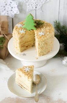 Een stuk napoleon-cake in kerstversiering op een lampje