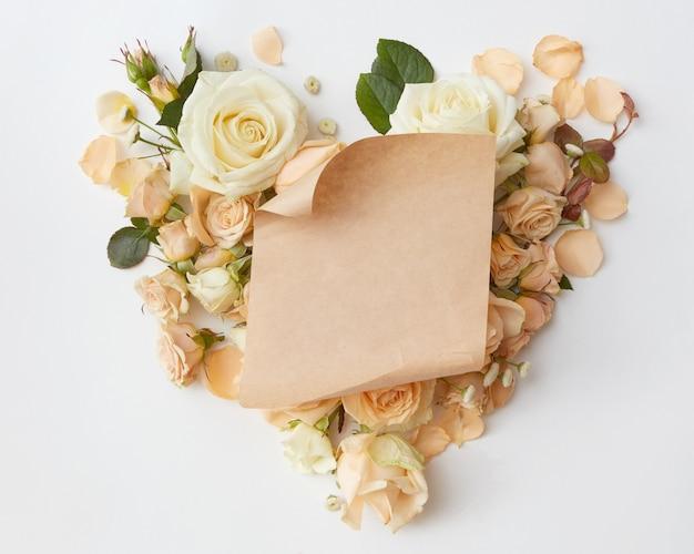 Een stuk papier maken in het hart van rozen geïsoleerd, plat gelegd