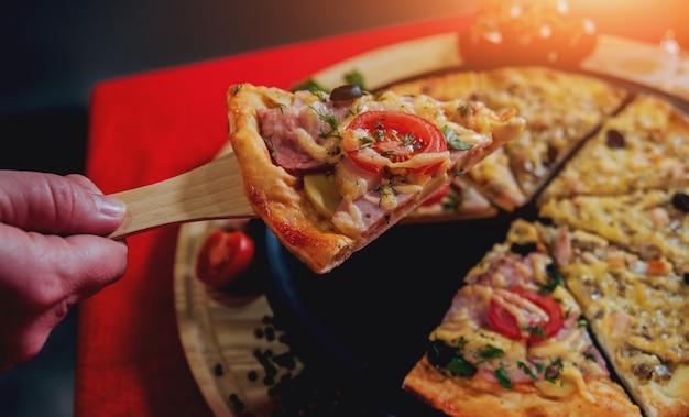 Een stuk pizza in zijn hand. een restaurant.